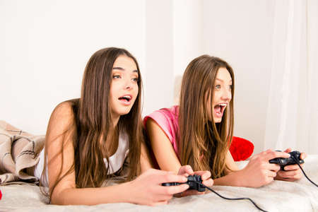 lesbo: Emotional pretty girl lying in bed and plaing video games
