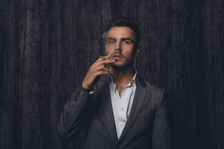 work addicted: Sexy brutal man in gray suit smoking a cigarette