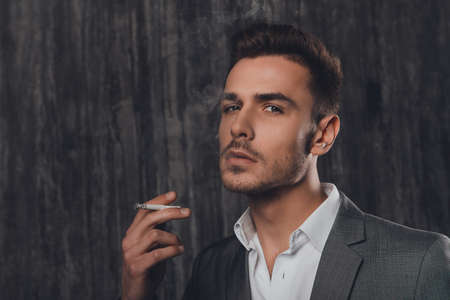 handome: Handome businessman in suit  smoking a cigarette on gray background