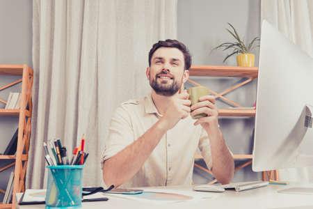 tomando café: hombre sonriente feliz que se sienta a la mesa y que sostiene la taza de café Foto de archivo