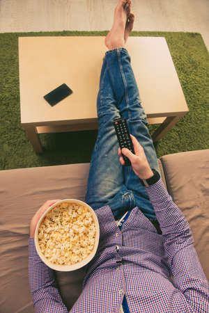 barefoot man: Top view of barefoot man lying on couch and watching tv with popcorn