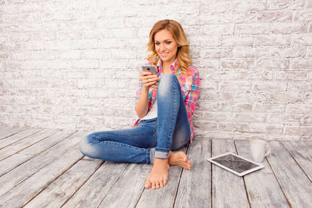 Happy young woman sitting  on floor with tablet, phone and cup