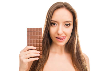 sweettooth: Pretty girl holding bar of chocolate and licking her lips