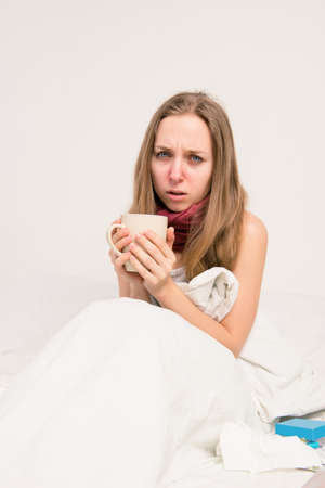 grippe: Portrait of upset sick woman with grippe holding cup of hot tea