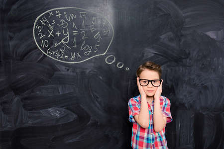 teorema: Retrato de joven escolar en vasos tratando de resolver tarea dif�cil Foto de archivo