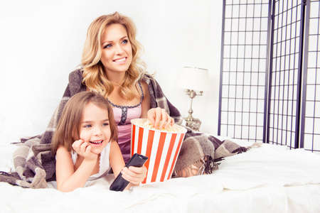 a cartoon film: Excited mom and daughter watching tv and eating  popcorn