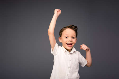 triumphing: Yes!  Happy little boy triumphing with raised hands Stock Photo