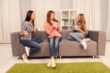 three friends: Attractive sisters sitting on couch and having talk with coffee