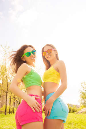 lesbo: Two sexy slim happy women in glasses and color clothes