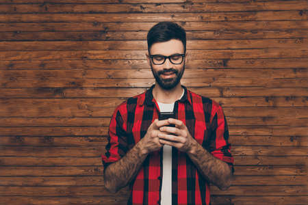 cute guy: Happy hipster man in glasses typing sms on phone Stock Photo