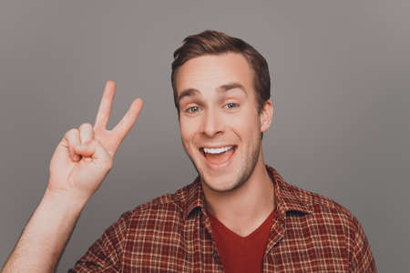 two fingers: Close up portrait of smiling man showing two fingers