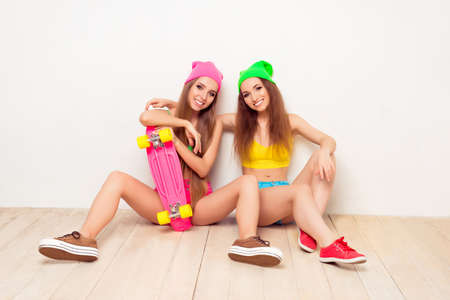 siting: Portrait of two happy stylish girls siting on floor with skate