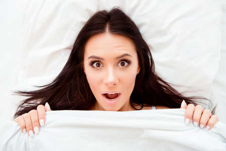 Top view portrait of shocked woman with open mouth after sleep
