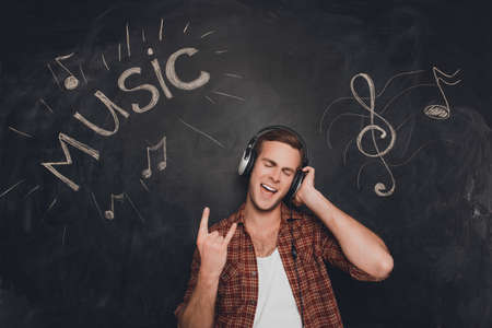 Portrait of man in headphones listening music and showing rock gesture Stock Photo
