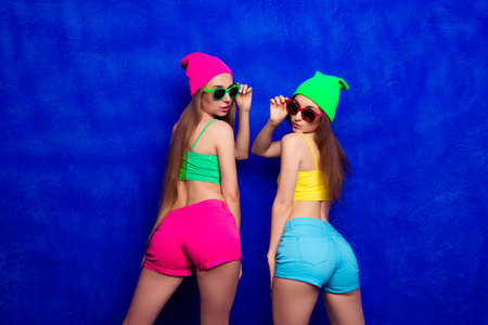 booty shorts: Beautiful young woman in color clothes and glasses showing backs