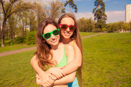 lesbo: Portrait of beautiful girls in glasses embracing in the park