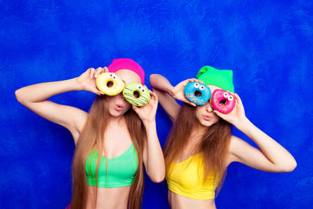 lesbo: Portrait of  smiling women covering eyes with donuts isolated on  blue background