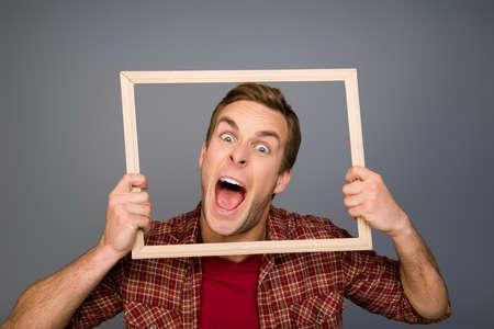 舌を示す木製のフレームを保持しているコミックの若い男