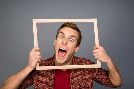 Comic young man  showing tongue and  holding wooden frame Stock fotó