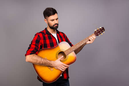 instrumentalist: Young handsome musician holding guitar and playing Stock Photo