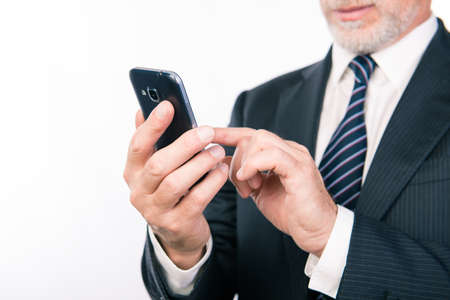 finance manager: Close up photo of aged businessman typing message on his smartphone