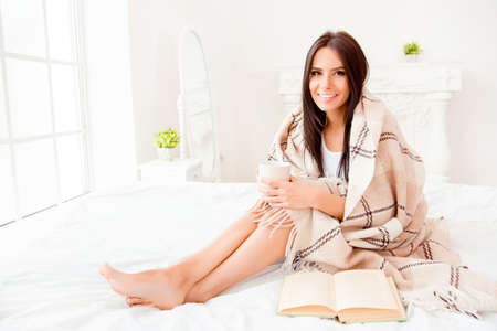 siting: Young woman reading book while siting on bed with cup of tea