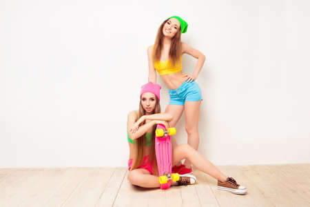 siting: Pretty hipster woman siting on floor with skate near her sister