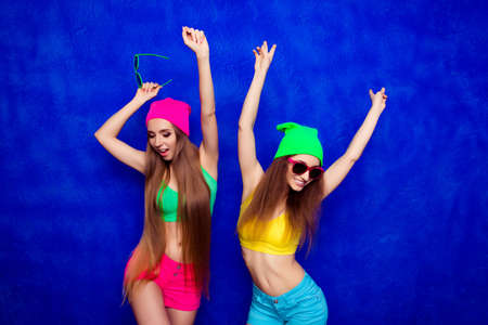 Two happy cheerful hipster women dancing with raised hands