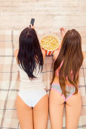 culo di donna: Vista dall'alto di due giovani donne sexy guardare la tv con popcorn Archivio Fotografico
