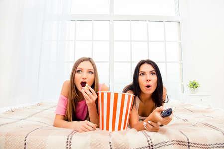 fiesta familiar: ¡Guauu! Dos niñas emocionados que ven la película y comiendo palomitas de maíz
