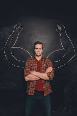 almighty: Serious young man with drawn muscular arms on the background of chalkboard