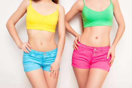 slim women: Close up photo of two women in color clothes showing fit slim body Stock Photo