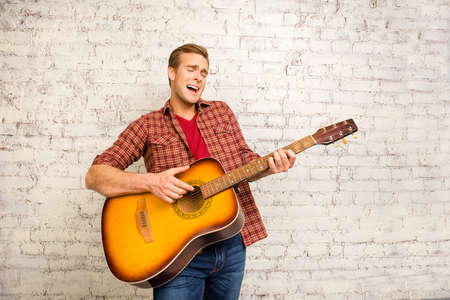 cute guy: Attractive singer giving concert and playing on the guitar Stock Photo
