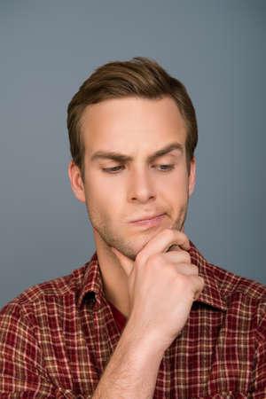 to ponder: Portrait of ponder handsome man dreaming on gray background