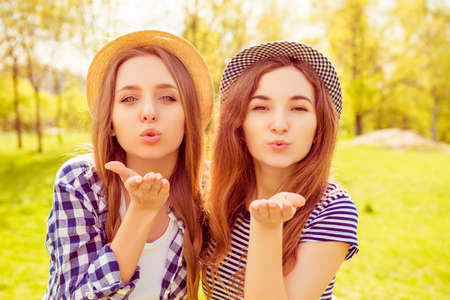 Portrait of beautiful girls in hats sending airy kiss