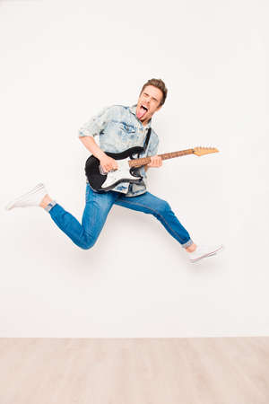 rocker: Young rocker playing on electro guitar, showing tongue  and jumping