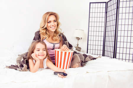 mom and daughter: Happy mom and little daughter watching tv with popcorn Stock Photo