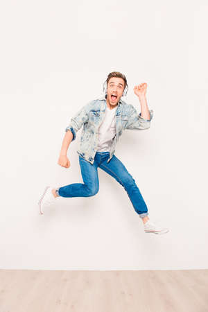Jonge energieke crazy man luisteren muziek en springen