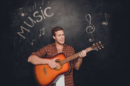 instrumentalist: Handsome young instrumentalist playing on the guitar and singer and smiling