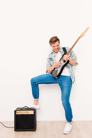 rocker: Young happy cool rocker playing on electric guitar
