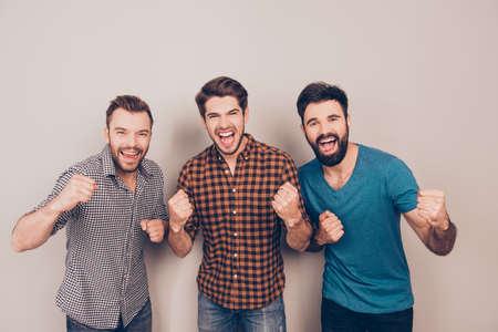 OUAIS! trois hommes criards beau montrant leurs mains fortes