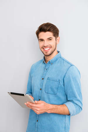 Happy handsome young man holding digital tablet Фото со стока