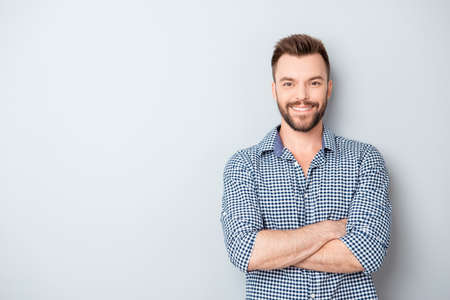 Happy smiling cheerful guy with crossed hands on gray background