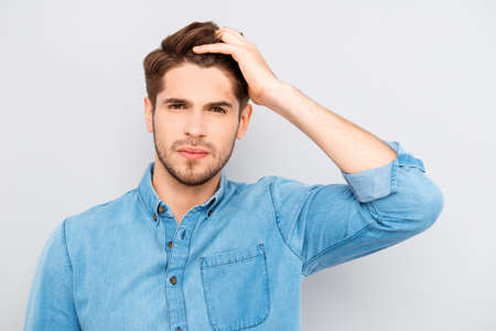Attractive man touching his hair on gray background Stock Photo