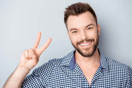 two fingers: Handsome man with beaming smile showing two fingers