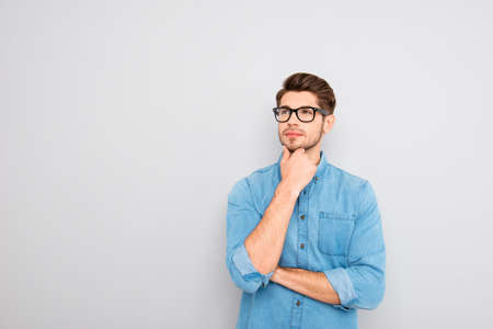 to ponder: Handsome ponder young businessman in glasses on gray background
