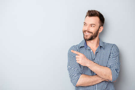 Cheerful handsome man showing direction and pointing with finger Stock Photo - 59056459