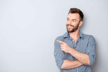 Fröhlich hübscher Mann zeigt Richtung und zeigt mit dem Finger