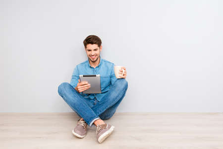 Handsome guy sitting on floor with tablet and crossing legs