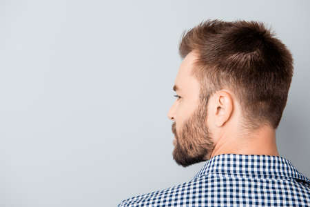 back view of man: Back view of young bearded brunet man on gray background